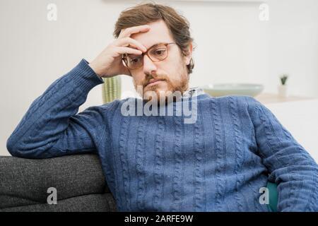 Depressiver Mann, der zu Hause auf dem Sofa sitzt, fühlt sich einsam an - Stockfoto