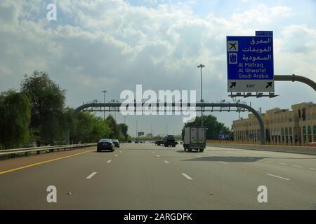 Dubai, VAE - 19. November 2019: Auf der modernen Autobahn zwischen Dubai und Abu Dhabi ist ein Straßenschild in arabischer und englischer Sprache gerichtet. - Stockfoto