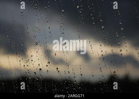 Regentropfen im Fensterbereich. Schwarzer, grauer, weißer Farbverlauf auf unscharfem Hintergrund. Bewölktes Regenwetter außerhalb des Fensters. Kühlung, Regen, schlechtes Wetter - Stockfoto