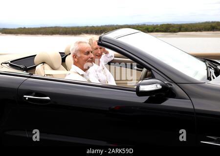Reifes Ehepaar: Nahbild eines Paares, das an einem Sommernachmittag mit dem Top Down in einem schwarzen Benz-Cabrio auf der Straße fährt. Aktion - Stockfoto