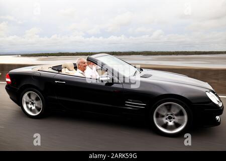 Reifes Ehepaar: Gut abseits reiferes Paar fährt an einem Sommernachmittag mit dem Top Down im schwarzen Benz Cabrio auf der Straße. Aktion - Stockfoto