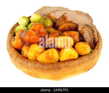 Roastbeef in einem Yorkshire Pudding mit gerösteten Kartoffeln und Gemüse isoliert auf weißem Hintergrund - Stockfoto