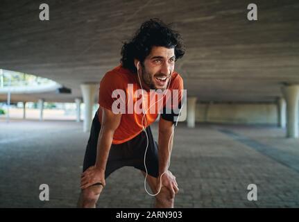 Porträt eines schwitzenden und müden jungen männlichen Fit, der nach dem Joggen in der Straße unter der Brücke eine Pause einlegen wird Stockfoto