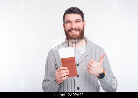 Foto des jungen gutaussehenden Mannes mit Bart, der Daumen nach oben zeigt und den Pass mit Karten hält, bereit für die Reise - Stockfoto