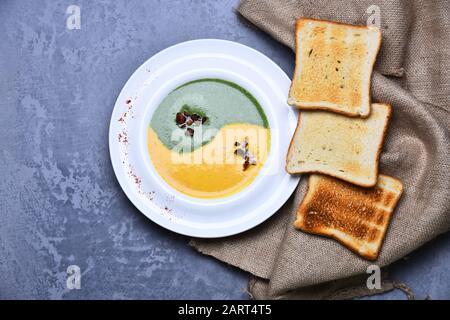 Spinat und Kürbiscremesuppe auf grauem Texturhintergrund. Traditionelles Küchenkonzept. Japanische Suppe in der Nähe von gebratenem Toastbrot und Burlap im Restaurant. Pürieren Sie in grün-gelber Farbe im Yin-Yang-Zeichen - Stockfoto