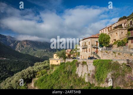 Niedrige, schwere Wolken über Gorges de Spelunca, zerhabene Steinhäuser in der Bergstadt Ota oberhalb der Schlucht, Corse-du-Sud, Korsika, Frankreich - Stockfoto