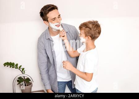 Vater mit Sohn, der Rasierschaum auf die Gesichter im Badezimmer auftragen - Stockfoto