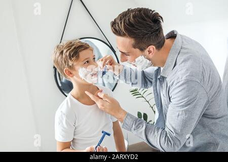 Vater und sein kleiner Sohn rasieren sich im Badezimmer - Stockfoto
