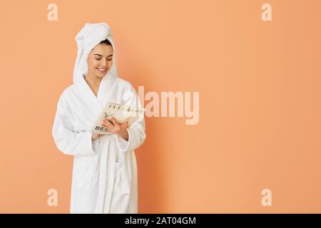 Schöne junge Frau nach Dusche Lesemagazin auf Farbhintergrund - Stockfoto