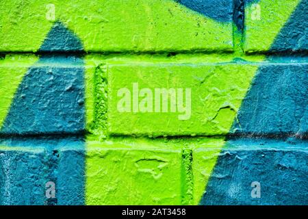 Ziegelwand mit abstraktem Muster aus türkisfarbenem und grünem Farbmuster. Hintergrund. Textur. - Stockfoto