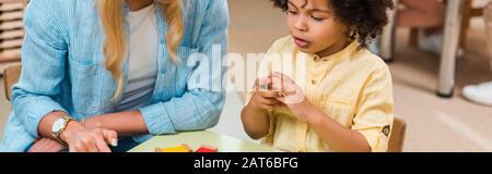 Panoramaaufnahme von afroamerikanischen Kindern, die in der montessori-schule ein pädagogisches Spiel spielen