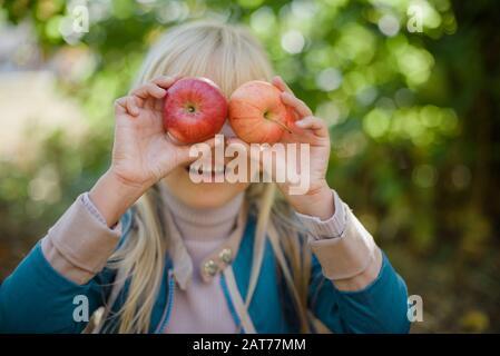 Portrait des Mädchens, das roten organischen apfel im Freien isst. Erntekonzept. Kind pflückt im Herbst Äpfel auf dem Bauernhof. Kinder und Ökologie. Gesunde Ernährung Ga Stockfoto
