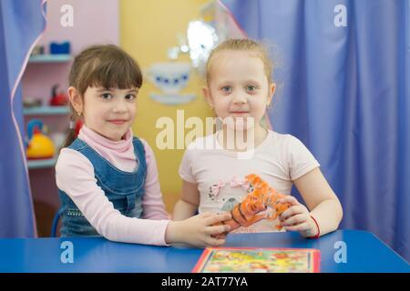 Weißrussland, die Stadt Gomel, 25. April 2019. Tag der offenen Tür im Kindergarten. Zwei sechs Jahre alte Mädchen mit Spielzeug. Freundinnen im Kindergarten.