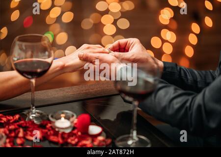 Ein Paar, das ein romantisches Abendessen und einen Überraschungsvorschlag in einem eleganten Restaurant mit schöner Dekoration hat. Romantik und Valentinstag Konzept - Stockfoto