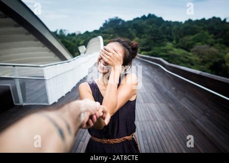 Lächelnde junge Frau, die auf einer Brücke steht und ihr Gesicht bedeckt und die Hand des Mannes hält. - Stockfoto