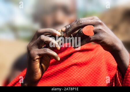 Afrikanischer Mann, der einen schwelenden Kuchen mit einem roten Herzring in den Händen hält. Tansania, Afrika. Selektiver Fokus. - Stockfoto