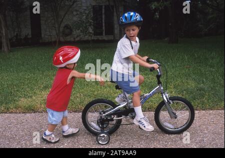 Austin, Texas: 5-jähriger Junge fährt Fahrrad mit Trainingsrädern, während 3-jähriger Bruder zurückgeht. ©Bob Daemmrich - Stockfoto