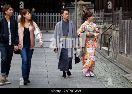Zwei junge Teenager (Mann und Frau) trugen einen Kimono auf der Straße in Kyoto, in der Nähe eines jungen Paares, das sich im modernen westlichen Stil kleidete. - Stockfoto
