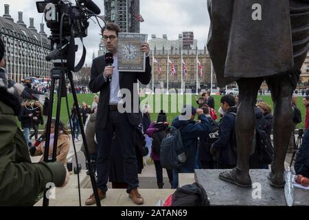Ein französischer TV-Reporter steht neben der Statue von Mahatma Gandhi und hält die Titelseite der Zeitung Times mit der Seite ein Bild von Big Ben, am Brexit Day, dem Tag, an dem Großbritannien die Europäische Union am 31. Januar 2020 rechtskräftig verlässt, in Westminster auf. In London, England. - Stockfoto