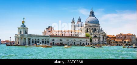 Panoramablick auf den Canal Grande mit Wassertaxis und die Kirche Santa Maria della Salute in Venedig, Italien. Motorboote sind der Haupttransport in Venedig.
