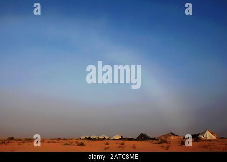 Der Nebelbogen kurvt am Himmel über das Zeltlager und die Sanddünen in der Sahara - Stockfoto