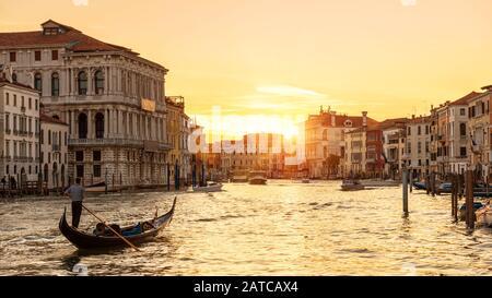 Venedig bei Sonnenuntergang, Italien. Gondel mit Touristen segelt nachts auf dem Canal Grande. Blick auf die Stadt Venedig bei Sonneneinstrahlung am Abend. Landschaft der sonnigen Straße in