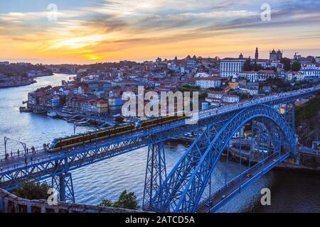 Porto, Portugal: BEI Sonnenuntergang fährt ein Zug auf der Dom Luis I Brücke über den Fluss Douro, der Porto und Vila Nova de Gaia verbindet und zwischen den Jahren 1881 und 188 gebaut wurde