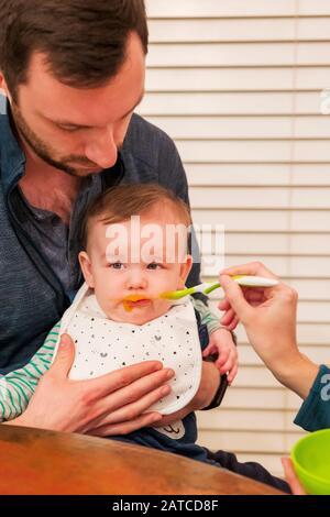 Eltern Löffel Fütterung sieben Monate alter Baby Junge - Stockfoto