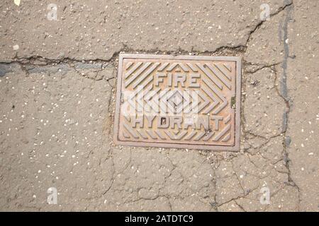 """Nahaufnahme der alten Metallmanlochabdeckung """"Feuerwehrhydrant"""" in der Asphaltstraße, Edinburgh, Schottland, Großbritannien - Stockfoto"""