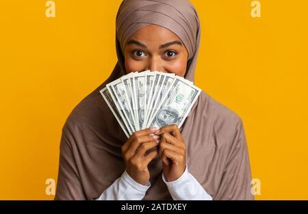 Freudige Afro-Frau In Hijab Versteckt Sich Hinter Dollar Cash Fan - Stockfoto
