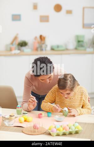 Vertikales Porträt von Mutter und Tochter, das Ostereier zusammen am Tisch im gemütlichen Kücheninneren malt, Kopierraum Stockfoto