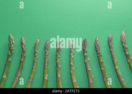 Grüner roher und gesunder Asparagus auf grünem Hintergrund. Entgiftung und Superfood-Konzept.