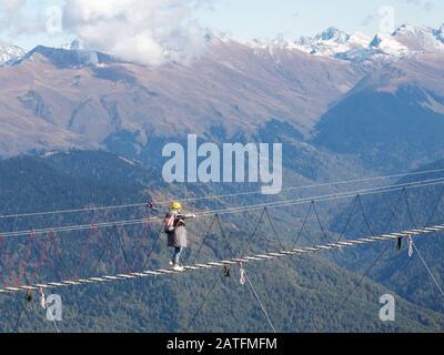 Ein Mädchen in einem gelben Helm und mit Rucksack überquert eine Hängebrücke über eine Klippe auf dem Grund verschneiten Berggipfels - Stockfoto