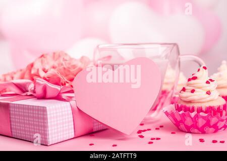 Valentinstaggeschenk in einer Schachtel, die in Streifenpapier verpackt ist und mit Seidenbandbogen und herzförmiger Grußkarte auf pinkfarbenem Ballonhintergrund mit Cop gefesselt ist - Stockfoto