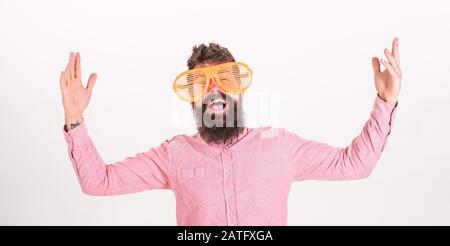 Mann mit Bart und Schnurrbart auf glücklichem Gesicht trägt lustige große Brillen, weißer Hintergrund. Fröhliches Stimmungskonzept. Hipper blickt durch eine riesige gestreifte Sonnenbrille. Kerl mit Bart hat Spaß. - Stockfoto