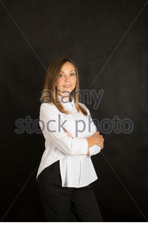 Porträt einer hübschen jungen Frau im Studio auf dunklem Hintergrund - Stockfoto