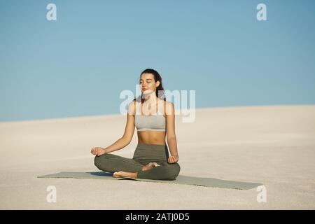 Junge Frau macht Yoga-Übungen am Strand. Junge Frau meditiert in Lotus-Pose in der Wüste. Entspannungsmeditationskonzept. Junge, gemischte asiatische Kaukasianerin, die im Freien Yoga in der Natur praktiziert. Flacher DOF-Kopierraum blauer Himmel weißer Sandhintergrund. - Stockfoto
