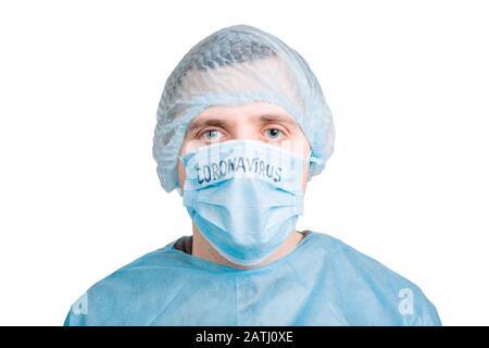 Porträt eines gutaussehenden Mannes mit medizinischer Uniform und Maske mit Coronavirus-Wort isoliert auf weißem Hintergrund. Schützen Sie Ihre Gesundheit. Coronavirus Konzept - Stockfoto