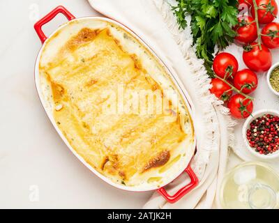 Cannelloni mit Füllung aus Ricotta und Petersilie, gebacken mit Béchamel-Sauce, Draufsicht, weißem Marmorhintergrund - Stockfoto