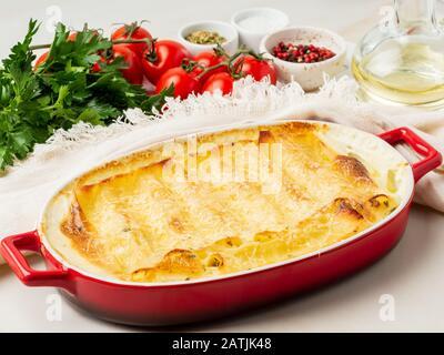Cannelloni mit Füllung aus Ricotta und Petersilie, gebacken mit Béchamel-Sauce, Seitenansicht, weißer Marmorhintergrund - Stockfoto