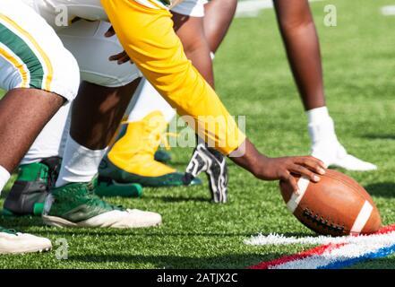 Ein High-School-Fußballzentrum ist ausgerichtet und bereit, den Ball zu schnallen, um das Spiel zu beginnen. - Stockfoto