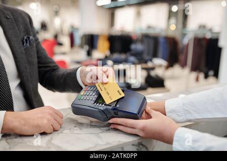 Nahaufnahme eines nicht erkennbaren Geschäftsmannes im Anzug, der an der Theke steht und mit kontaktloser Karte im Geschäft bezahlt - Stockfoto