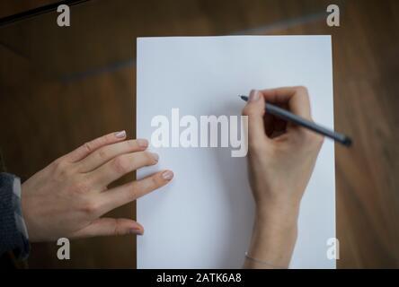 Weibliche Hand, die einen Stift hält und auf einem leeren weißen Blatt Papier mit Kopierbereich schreibt. RF-Schreiben, notieren, beginnen, Geschäftskonzept - Stockfoto