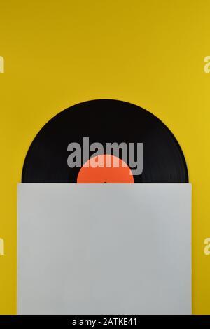 Alte schwarze Schallplatte mit leerem orangefarbenem Label, halb aus der weißen leeren Abdeckung auf gelbem Hintergrund