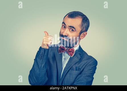 Mann im Anzug, Geschäftsmann zeigt wie Daumen nach oben und zeigt mit dem Finger nach oben auf den seitlichen Kopierbereich, der auf die Kamera blickt und überzeugt, dass dies die richtige Richtung ist - Stockfoto