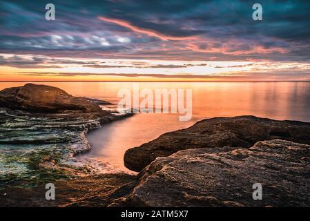 Malerischer Sonnenaufgang über einem felsigen Strand. - Stockfoto