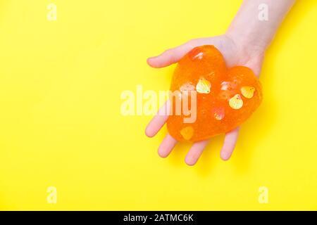 Orangefarbener Schleim in Herzform in Kinderhänden. Mädchen Hände spielen Slime Spielzeug auf gelbem Hintergrund. Slime machen. Copyspace. Liebe und Valentinstag Konzept - Stockfoto