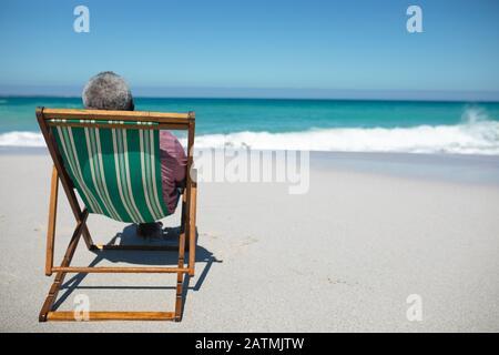 Der alte Mann erholt sich am Strand Stockfoto