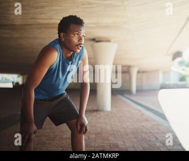 Ein afrikanisch-amerikanischer männlicher Läufer, der am Morgen auf der Straße unter der Brücke atmet Stockfoto