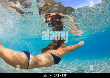 Aktive junge Frau taucht, schwimmt unter Wasser, um tropische Fische im Meerlagunenpool zu sehen. Badeaktivität, Wassersport auf Sommer-Strandfahrt mit Kindern - Stockfoto